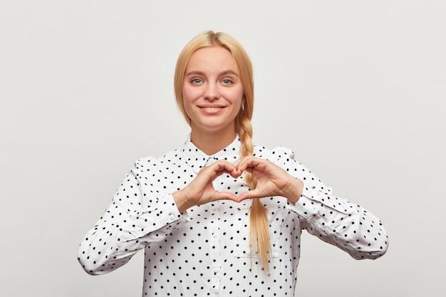 Mooie jonge vrouw toont emotie op een witte achtergrond. het meisje toont het gebaar van de hartvorm Gratis Foto