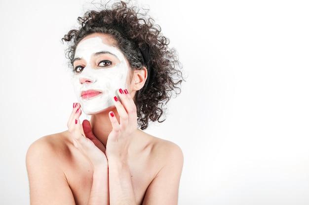 Mooie jonge vrouw wat betreft haar gezichtsmasker dat op witte achtergrond wordt geïsoleerd Gratis Foto