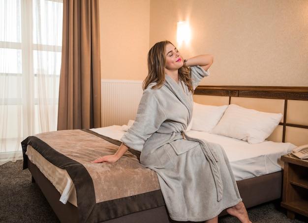 Mooie jonge vrouw zittend op bed die zich uitstrekt glimlachen Gratis Foto