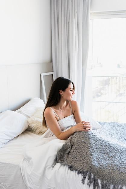 Mooie jonge vrouw zittend op bed met grijs tapijt Gratis Foto