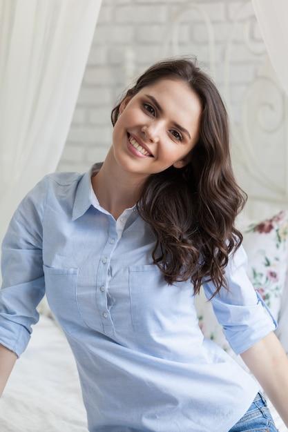Mooie jonge vrouw zittend op bed Premium Foto