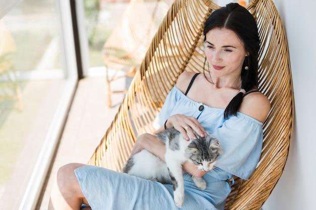 Mooie jonge vrouw zittend op een stoel met haar schattige kat Gratis Foto