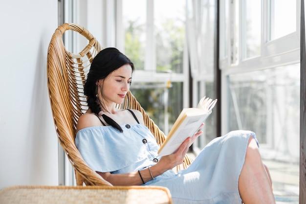 Mooie jonge vrouw zittend op stoel leesboek Gratis Foto