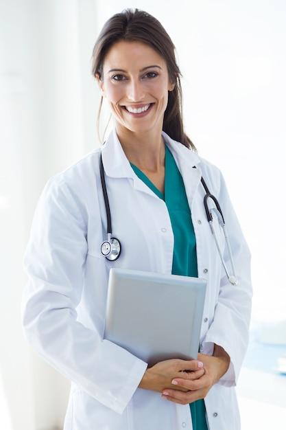 Mooie jonge vrouwelijke arts die camera in het bureau bekijkt. Gratis Foto