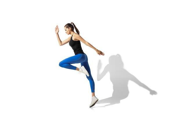 Mooie jonge vrouwelijke atleet die zich uitstrekt, training op witte ruimte, portret met schaduwen Gratis Foto