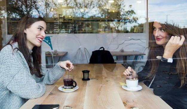 Mooie jonge vrouwen drinken thee in een koffiewinkel. Gratis Foto