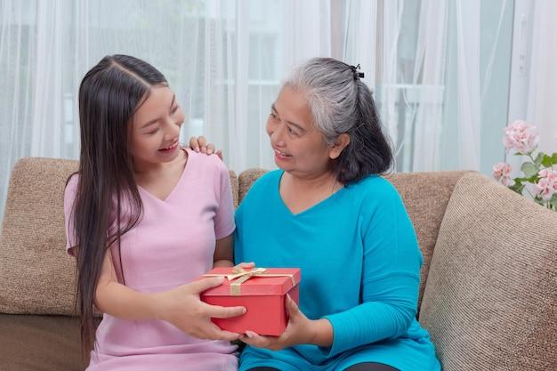 Mooie jonge vrouwen geven geschenken aan moeders. Gratis Foto