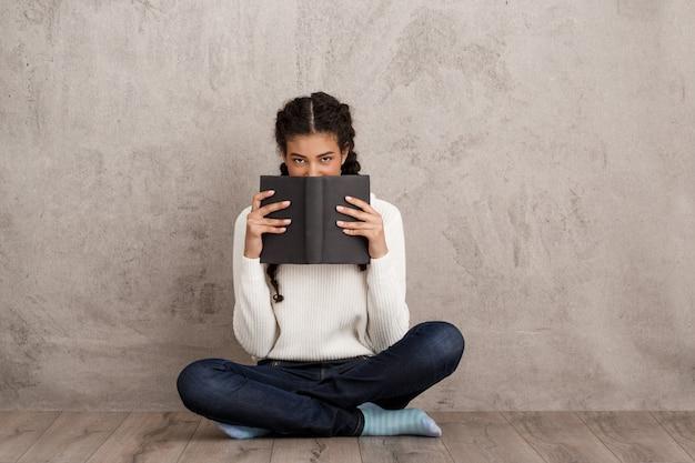 Mooie jonge vrouwen verbergende mond achter boek over beige muur Gratis Foto