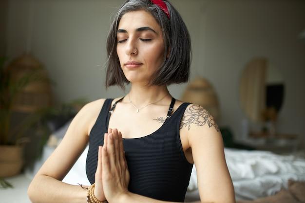 Mooie jonge womanwith grijsachtig haar, tatoeage op schouder en neusring die handen samen in namaste bij hartchakra drukken Gratis Foto