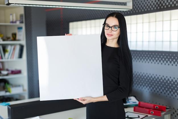 Mooie jonge zakenvrouw in zwarte jurk en glazen houden lege poster Premium Foto