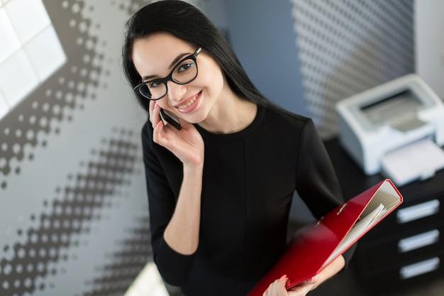 Mooie jonge zakenvrouw in zwarte jurk en glazen houden papieren map Premium Foto