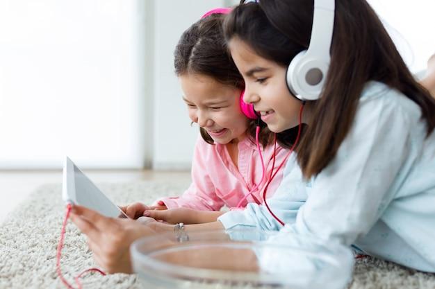 Mooie jonge zussen luisteren naar muziek met digitale tablet a Gratis Foto