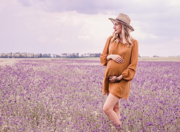 Mooie jonge zwangere vrouw in hoed op lavendel veld. bloeiende bloemen Premium Foto
