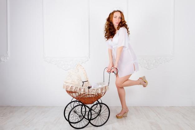 Mooie jonge zwangere vrouwentiener in witte kleding met kinderwagen Premium Foto