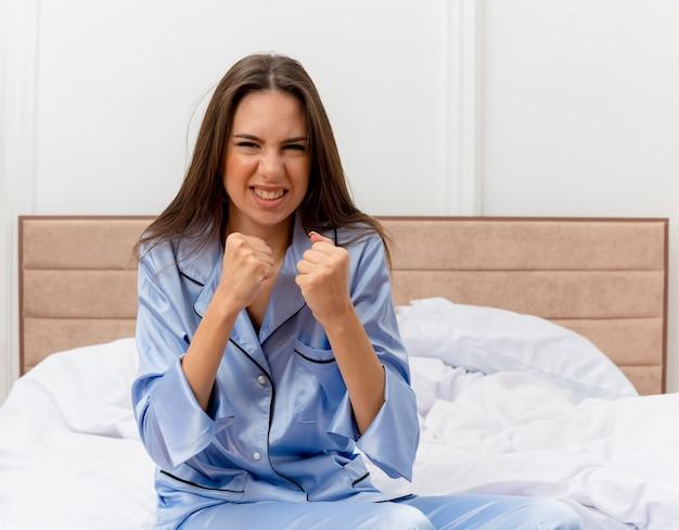 Mooie jongedame in blauwe pyjama zittend op bed kijken camera balde vuisten met boos gezicht in slaapkamer interieur op lichte achtergrond Gratis Foto