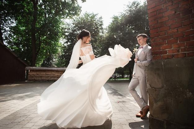 Mooie jonggehuwde paar wandeling in de buurt van oude christelijke kerk Premium Foto