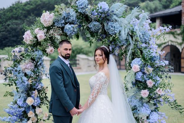 Mooie kaukasische bruidspaar staat voor versierd met blauwe hortensia boog en hand in hand samen Gratis Foto