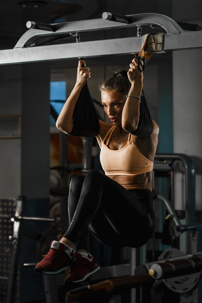 Mooie kaukasische fitness vrouw training met trx fitness riemen. schorsing oefenen in de sportschool Premium Foto