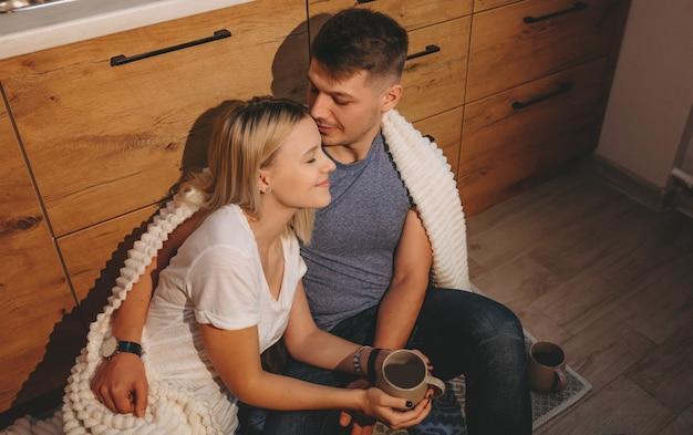 Mooie kaukasische paar zittend op de vloer in de keuken en samen een kopje thee drinken Premium Foto