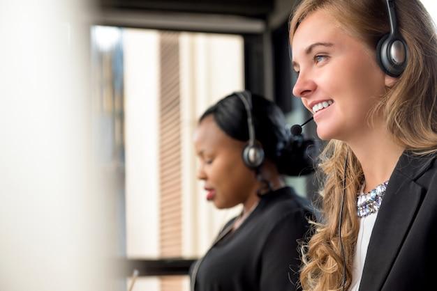 Mooie kaukasische vrouw die in call centre met internationale collega's werkt Premium Foto