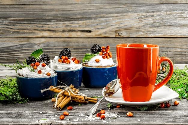 Mooie kerst cupcake met room en bessen op houten tafel kaneelkegels Gratis Foto