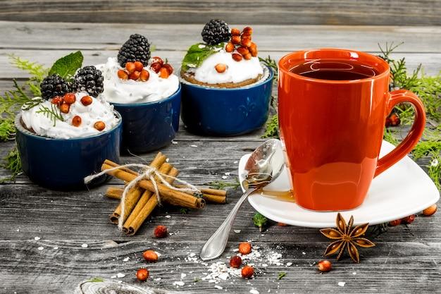 Mooie kerst cupcake met slagroom en bessen op houten achtergrond kaneel kegels Gratis Foto