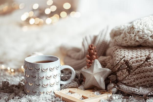 Mooie kerstbeker met een warme drank op een lichte onscherpe achtergrond. het concept van wooncomfort en warmte. Gratis Foto