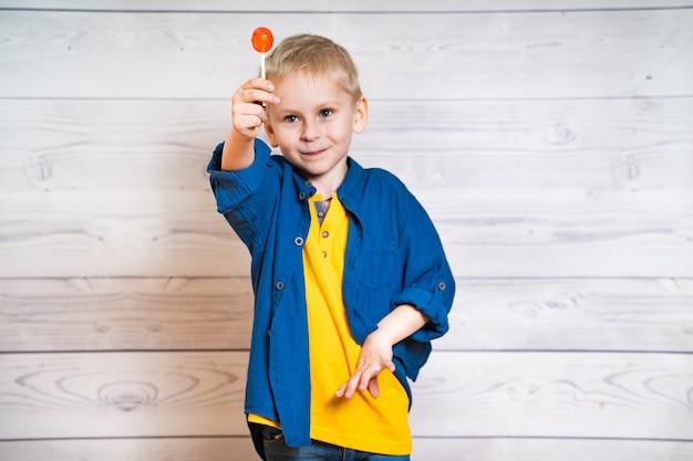 Mooie kleine jongen met een lolly in handen Premium Foto