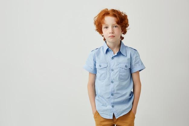 Mooie kleine jongen met gember haar en sproeten hand in hand in de zak Gratis Foto