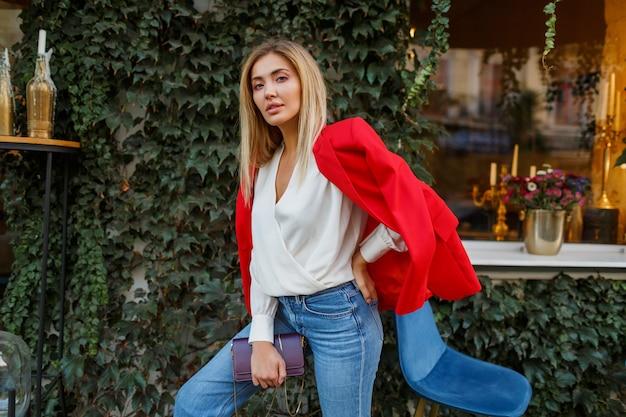 Mooie knappe blonde vrouw in rode jas poseren in stadscafé Gratis Foto