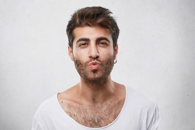 Mooie knappe jongen flirten met meisje blaast haar kus. ongeschoren man met een aantrekkelijk uiterlijk die zijn vriendin medeleven toont die haar gaat kussen. macho man Gratis Foto