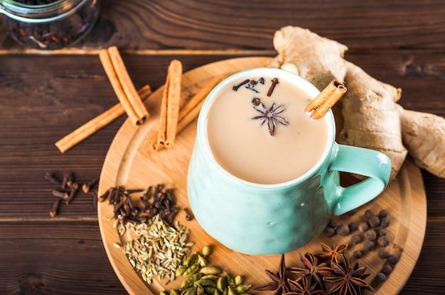 Mooie kop thee met melk, steranijsplant, kaneel op een houten achtergrond. Premium Foto