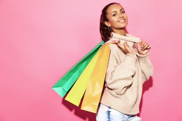 Mooie lachende prachtige vrouw. vrouw die zich in modieuze witte sweater bevindt en het winkelen zakken, op roze muur houdt. Gratis Foto