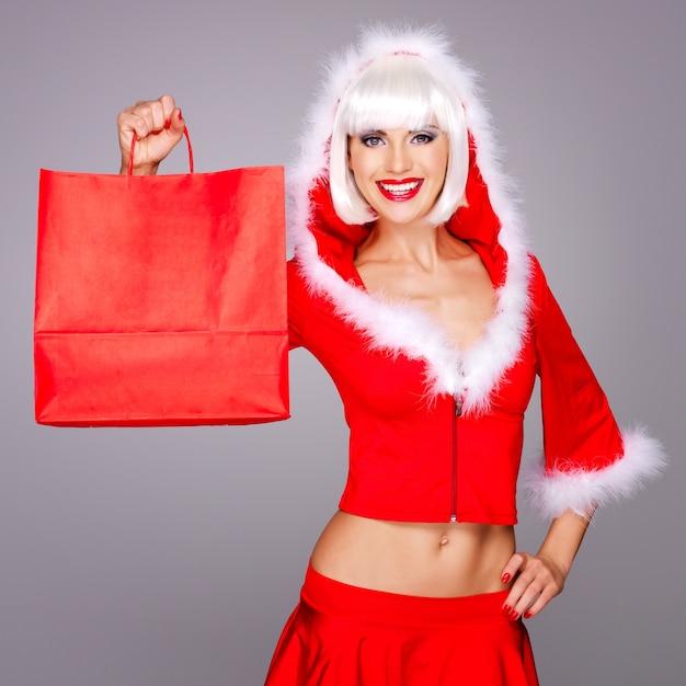 Mooie lachende vrouw in sneeuw maiden pak houdt de boodschappentassen Gratis Foto