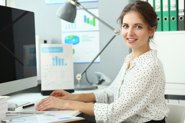 Mooie lachende vrouw zitten in kantoor Premium Foto