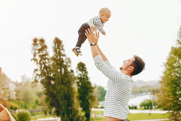 Mooie lange en stijlvolle vader in een trui en een spijkerbroek beukt met zijn kleine lieve zoon Gratis Foto