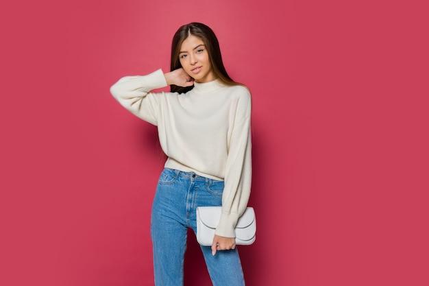 Mooie langharige vrouw in gezellige witte pullover en casual jeans poseren op roze achtergrond isoleren. holding eco lederen handtas. Gratis Foto
