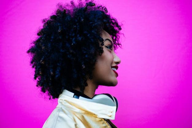 Mooie latijnse vrouw met krullend haar, portret dat in de stad wordt geplaatst Premium Foto