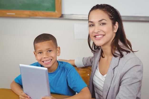 Mooie leraar en leerling met tablet aan zijn bureau Premium Foto