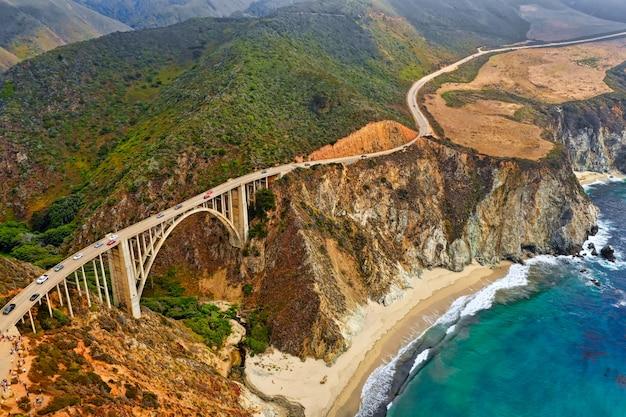 Mooie luchtfoto van groene heuvels en een bochtige smalle brug die langs de kliffen gaat Gratis Foto