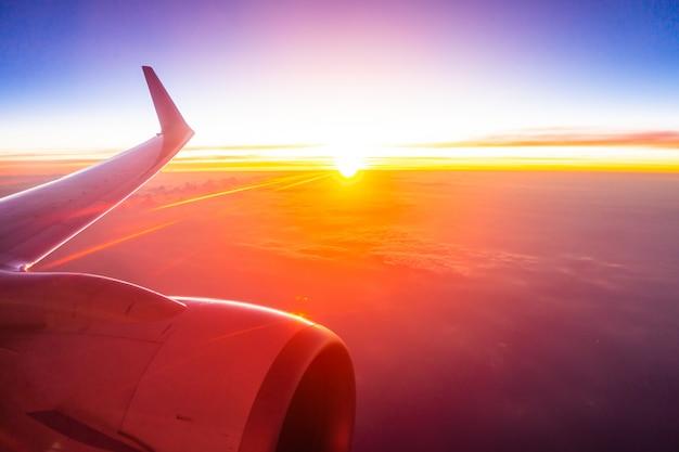 Mooie luchtmening van vliegtuigvleugel op witte wolk en hemel in zonsondergangtijd Gratis Foto