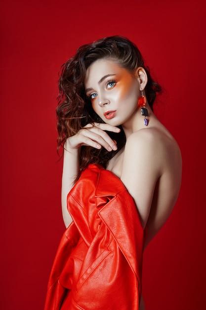 Mooie make-up van sexy naakt vrouw in rode jas op rood Premium Foto