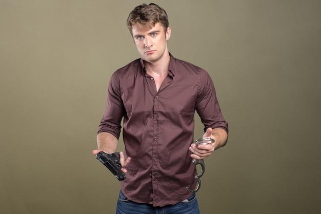 Mooie man met pistool en handboeien. geïsoleerd Premium Foto