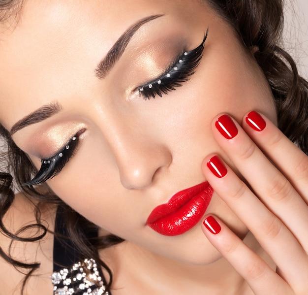 Mooie mannequin met rode nagels, lippen en creatieve oogmake-up - Gratis Foto