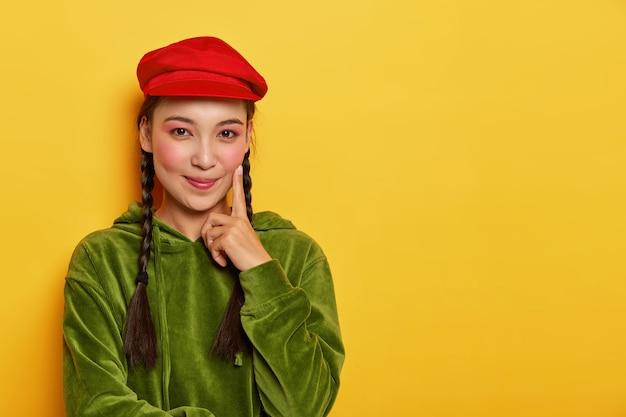 Mooie meid met een aziatische uitstraling, minimale make-up, raakt de wang met wijsvinger, ziet er positief uit, brengt graag vrije tijd door met winkelen Gratis Foto