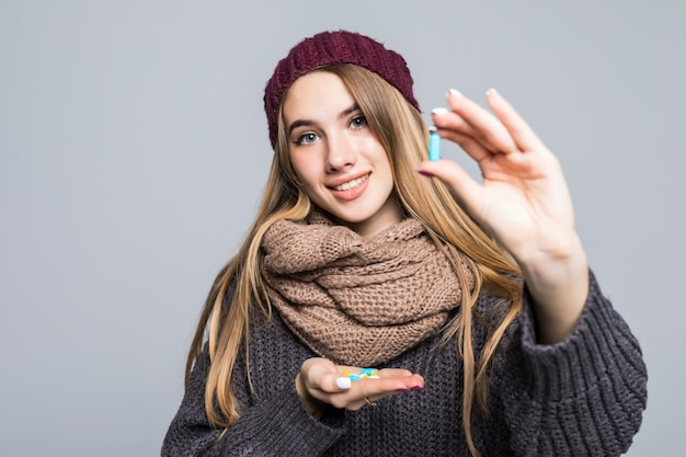 Mooie meiden met griep of verkoudheid hebben veel medicijnen om pillen te nemen om gezond te worden op grijs Gratis Foto