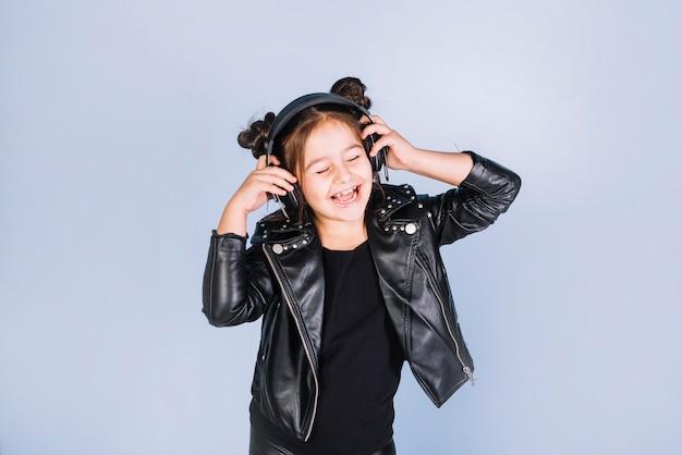Mooie meisje het luisteren muziek op hoofdtelefoon die zich tegen blauwe achtergrond bevinden Gratis Foto