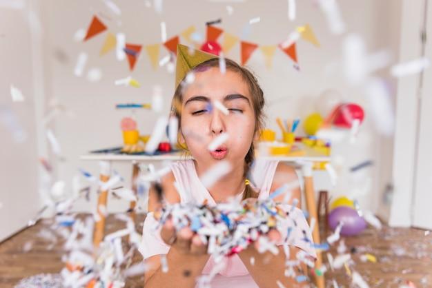 Mooie meisjes blazende document confettien op haar hand Gratis Foto