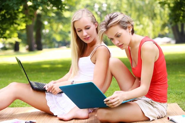 Mooie meisjes die laptops met behulp van bij een park Gratis Foto