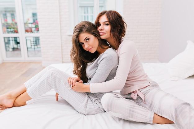 Mooie meisjes in pyjama's op bed. meisje met krullend haar knuffelt van achter een ander meisje, ze zijn op zoek. Gratis Foto